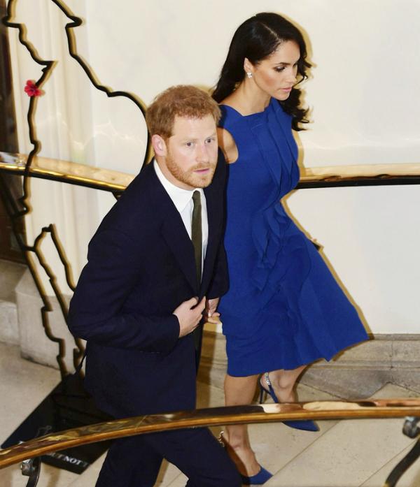 Dường như lo sợ vợ bị trượt ngã vì đi giày cao gót, Công tước xứ Sussex siết chặt tay Meghan đi cẩn thận từng bước lên cầu thang.