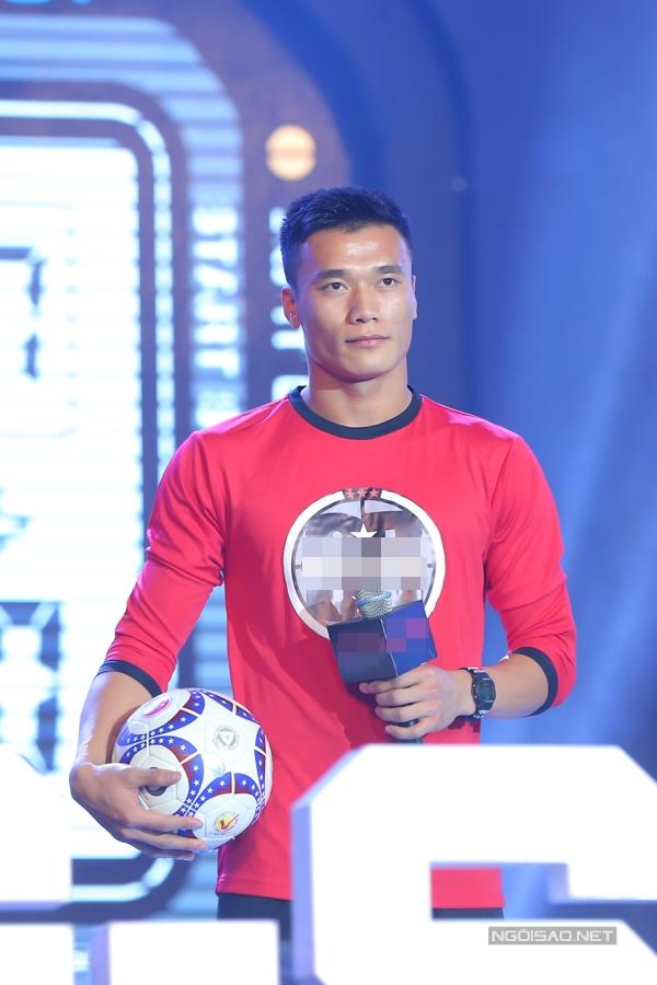 Anh diện trang phục thể thao năng động, tay cầm trái bóng có chữ ký của mình.