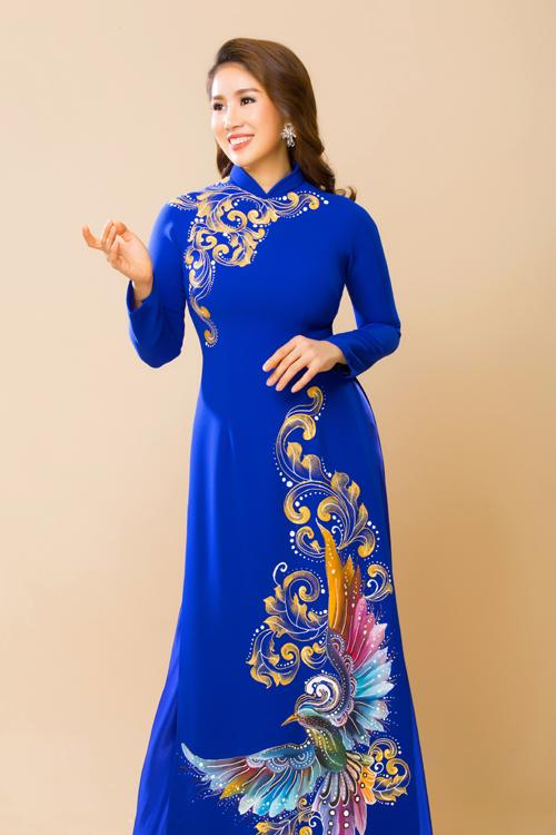 Chiếc áo dài có hình ảnh phượng hoàng được vẽ tay tỉ mỉ trên nền vải xanh cô ban. Bộ áo dài cưới được mặc với quần cùng tông, phù hợp cho cảcô dâu và mẹ cô dâu, chú rể.