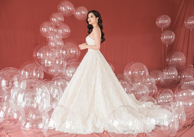 Hoa hậu diện váy quây cúp ngực được đính họa tiết lông vũ dọc thân váy. Mẫu váy bồng công chúa dễ dàngđốn timcác nàng dâu sắp bước chân về nhà chồng.