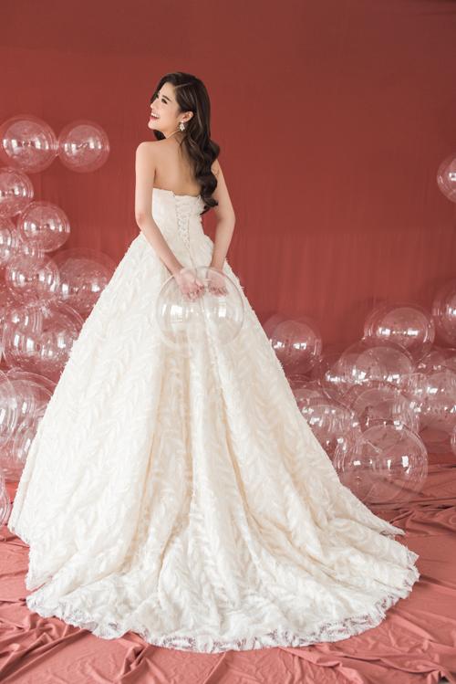 Đằng sau váy cưới đượcthắt nơ để ôm khít thân hình người mặc, tạo dáng corset gợi cảm.Phom váy truyền thống với tà váy dài làm vừa lòng cô dâu kỹ tính, tôn lên vòng eo con kiến của tân nương.