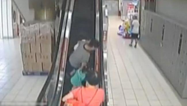 Người bà đi giữa dắt theo hai cháu bị mất thăng bằng và ngã trên thang cuốn ở siêu thị thành phố Bồng Lai, tỉnh Sơn Đông, Trung Quốc hôm 30/8. Ảnh: China Central TV.