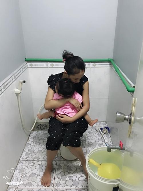 Bé Tine, 10 tháng tuổi, theo mẹ vào tận toilet.
