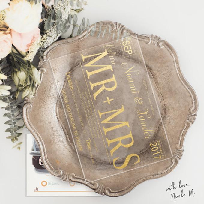 Một tấm thiệp cưới được viết bởi mực acrylic màu vàng gold cùng phông chữ cứng cáp, mạnh mẽ.