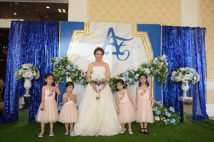 Cô dâu Thu Trang chọn váy quây trắng cúp ngực cho ngày đại hỷ của mình. Các phù dâu nhí diện váy hồng pastel tạo sự đối lập nhẹ nhàngvới màu sắc của tiệc cưới.