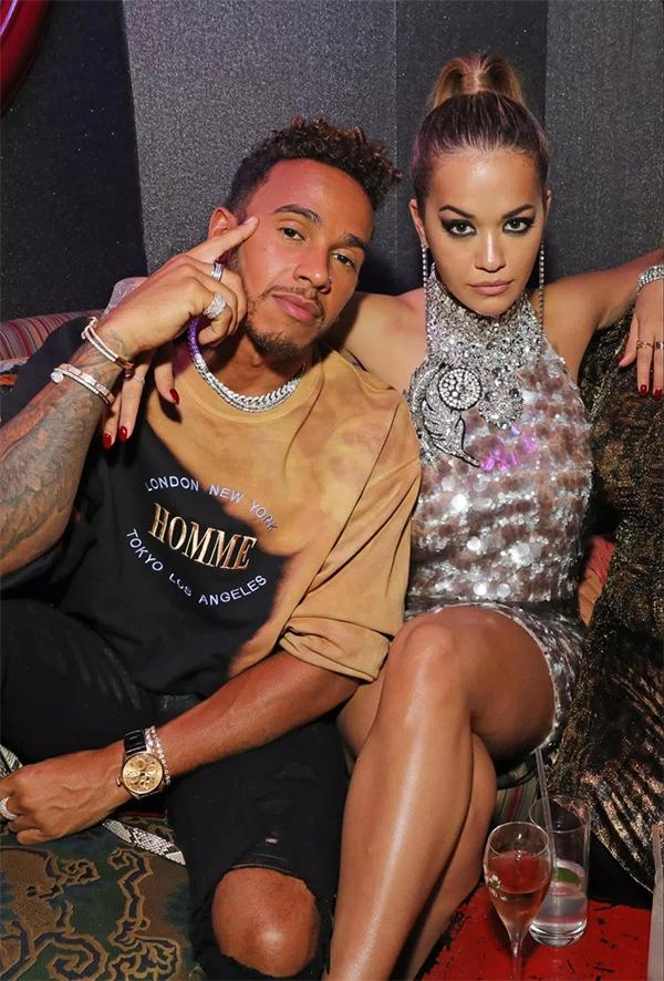 Hamilton chụp ảnh chung với nữ ca sĩ Rita Ora tại Tuần lễ thời trangLondon năm ngoái. Anh vẫn thường xuyên tiếp xúc với các người đẹp nhưng chưa bắt đầu một mối quan hệ hẹn hò nào sau khi chia tay NicoleScherzinger. Ảnh: GC.