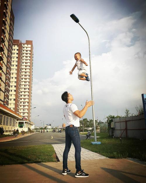 Con trai Quốc Nghiệp thích thú khi được bố tung hứng lên cao.