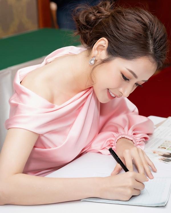 Người đẹp vui vẻ ký tặng cho các fan teen và khách mời dự event.