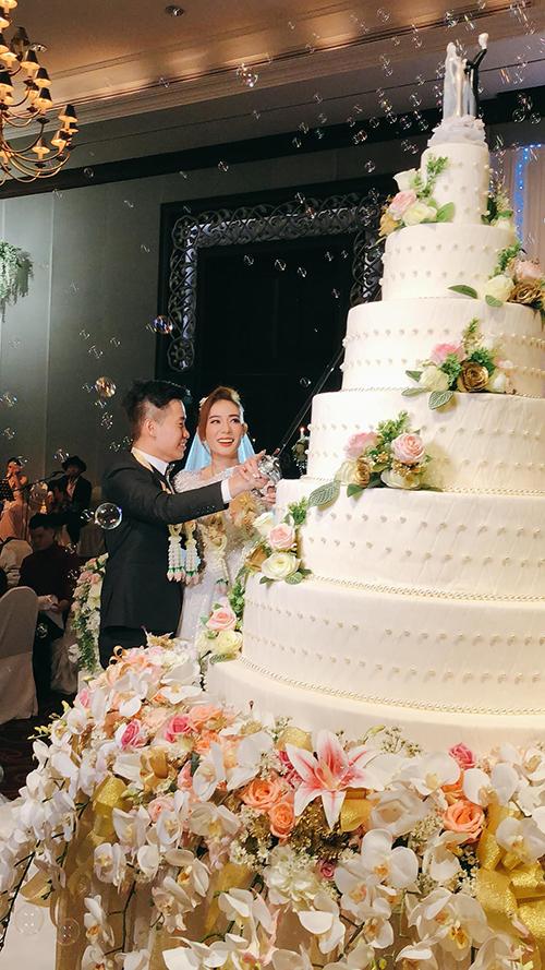 Bánh cưới màu trắng 5 tầng của hai vợ chồng được tô điểm bởi hoa tươi, tượng mô phỏng cô dâu chú rể. Ảnh: Thái Đinh.
