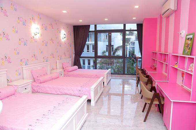 Phòng ngủ của 3 cô con gái mang tông hồng ngọt ngào. Các bé được bố mẹ sắm giường, bàn học và tất cả vật dụng giống hệt nhau.