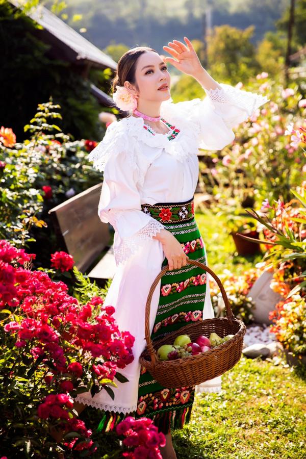 Người đẹp hóa thân cô gái Romania xách giỏ đi hái trái cây trong vườn.