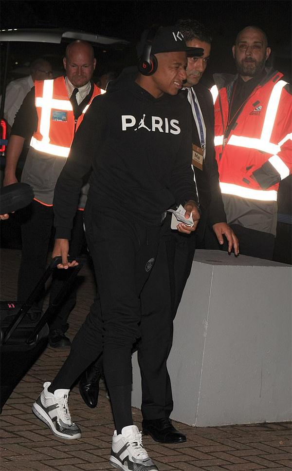 Mbappe rảo bước vào sân bay dưới sự hộ tống của nhân viên an ninh.