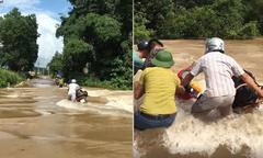 Dắt xe máy qua dòng lũ chảy xiết, người đàn ông suýt bị cuốn trôi
