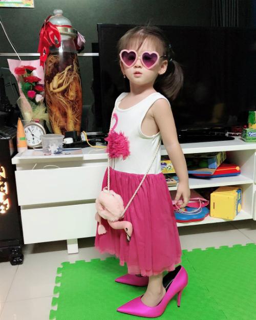 Con gái Trang Trần sành điệu khi đeo mắt kính, đi giày của mẹ. Người mẫu nhắn nhủ: Là con gái của mẹ con chỉ việc ăn học và vô tư. Cuộc đời luôn màu hồng như màu áo con.