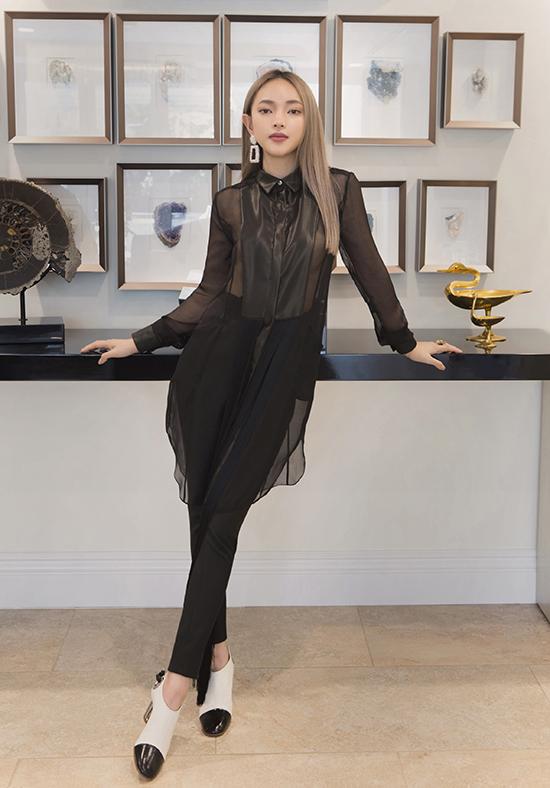 Trong một look khác, Châu Bùi diện sơ mi dáng dài mỏng tanh bằng voan đen, kết hợp với chi tiết thân áo bằng lụa cách điệu, quần tây skinny và đôi ankle bốt trắng đen.