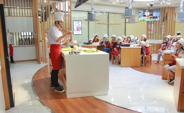 Thầy giáo hướng dẫn chuẩn bị nguyên liệu và các bước làm bánh.