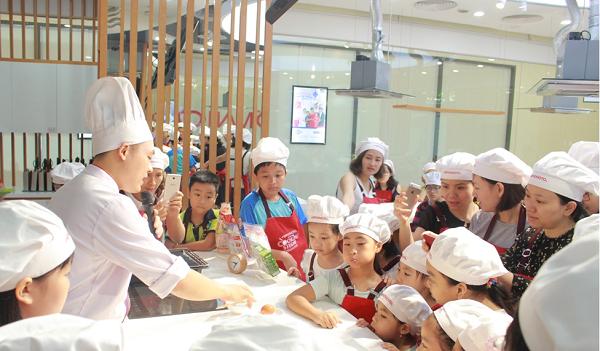 Thầy giáo hướng dẫn các bạn nhỏ làm hỗn hợp tạo màu cho bánh
