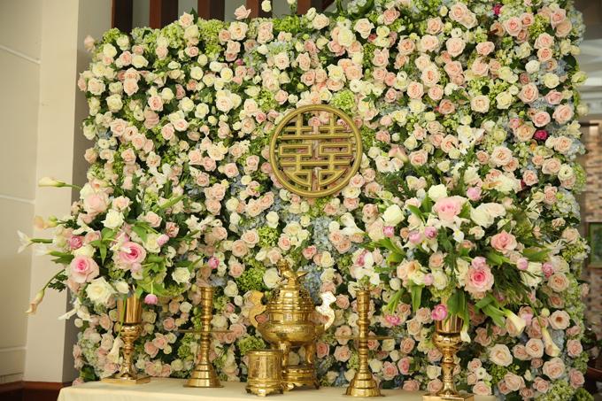 Bàn thờ gia tiên nhà gái trang trí bằng hàng trăm bông hoa tươi bên cạnh đặt các lư đồng sáng bóng.