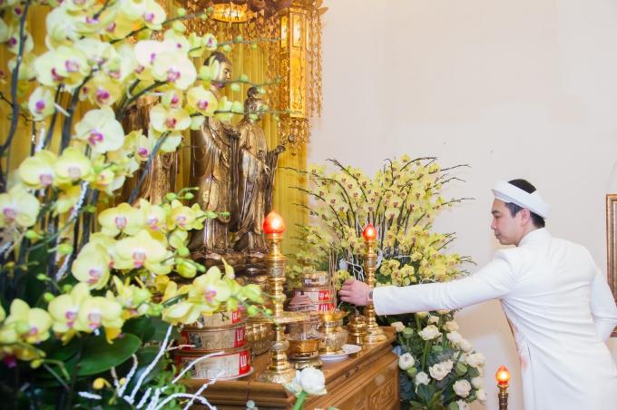 Bàn thờ Phật được trang trí với hoa lan màu vàng.