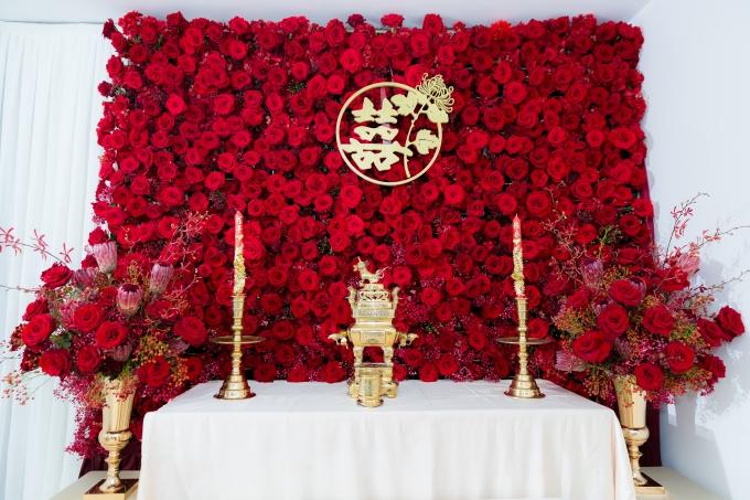 Bàn thờ gia tiên được trang trí bức tường hoa hồng Ecuador đỏ rực. Toàn bộ hoa sử dụng trang trí được nhập ngoại hoàn toàn với quy trình bảo quản khắt khe, đảm bảo cho hoa tươi lâu và giữ nguyên màu sắc như vừa cắt từ vườn.
