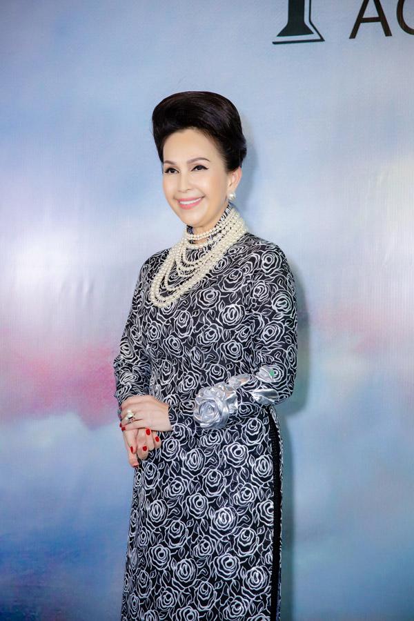 Diễn viên Diễm My cũng có mặt tại buổi khai trương showroom áo dài của NTK Kenny Thái. Để tăng thêm độ sang trọng, chị mixbộ vòng cổ ngọc trai đắt đỏ với trang phục áo dài họa tiết hoa hồng đen - trắng.
