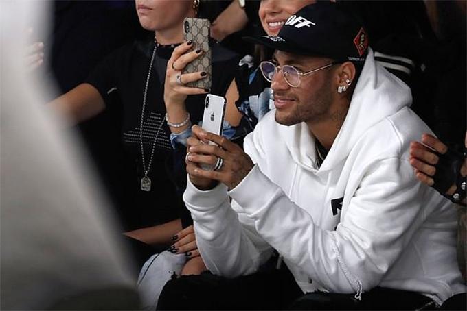 Neymar diện áo khoác nỉ màu trắng, quần jeans màu đen, đội mũ lưỡi trai, đeo kính thời trang và nhiều phụ kiện như hoa tai, nhẫn, vòng cổ....