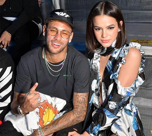 Neymar cởi áo khoác khoe các phụt kiện thời trang như vòng cổ, vòng tay, đồng hồ... chụp ảnh cùng bạn gái tại hậu trường show thời trang.