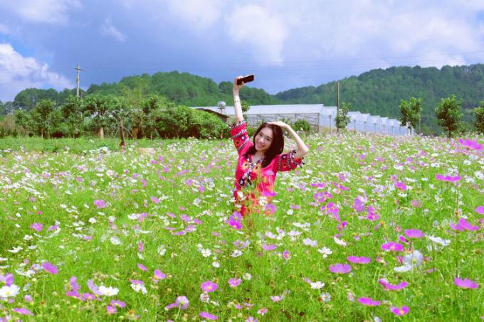 Elly Trần rạng rỡ pose hình giữa vườn hoa.