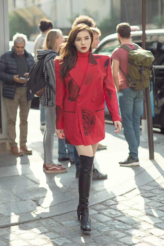 Hoa hậu chọn vest vai ngangmàu đỏ bắt mắt, thuộc bộ sưu tập Domino 68 vừa trình làng vào tháng 8 của hai nhà thiết kế Vũ Ngọc & Son để chưng diện.