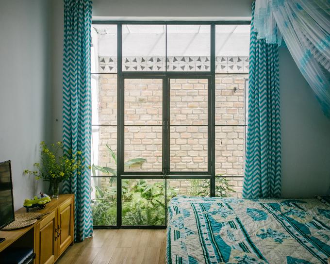 Phòng ngủ với những ô cửa kính hứng ánh sáng tự nhiên và nội thất màu dịu nhẹ.