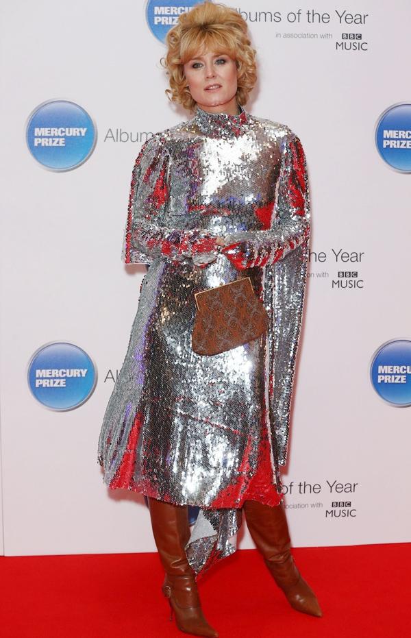Ca sĩ người Ireland - Róisín Murphy - thách thức mọi stylist khi kết hợp váy sequin lấp lánh cùng bốt da cổ cao màu nâu và túi đựng tiền xu phiên bản cỡ lớn.
