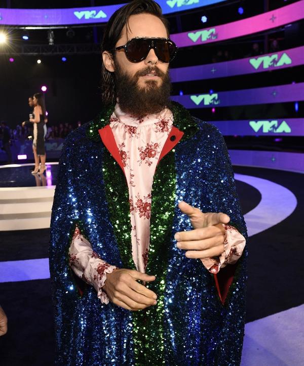 Diễn viên Suicide Squad Jared Leto giúp mình nổi bật bằng mẫu áo choàng đính kim sa phối màu sặc sỡ, kết hợp áo lụa họa tiết hoa của phụ nữ.