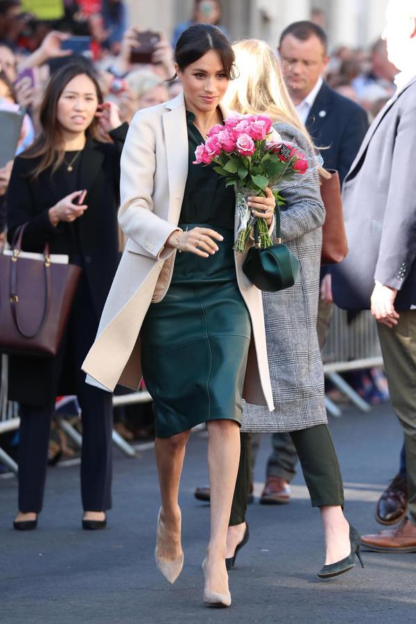 Meghan ghi điểm bởi phong cách thanh lịch với sơ mi và chân váy ton-sur-ton xanh, kết hợp áo choàng, giày cao gót màu nude nền nã. Tổng giá trị set đồ của cô là 4.780 bảng Anh (145 triệu đồng).