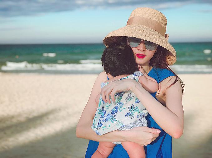 Hoa hậu Đặng Thu Thảo bế con gái dạo chơi trên biển.