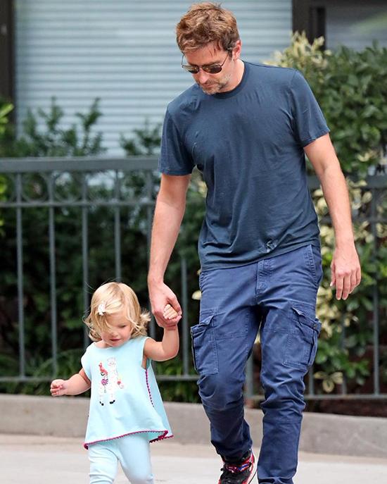 Bradley Cooper dắt tay con gái 1 tuổi rưỡi trên phố hôm 2/10. Anh mặc bộ đồ thoải mái, trên áo lấm lem vết màu trắng giống như bị dính sữa bột.