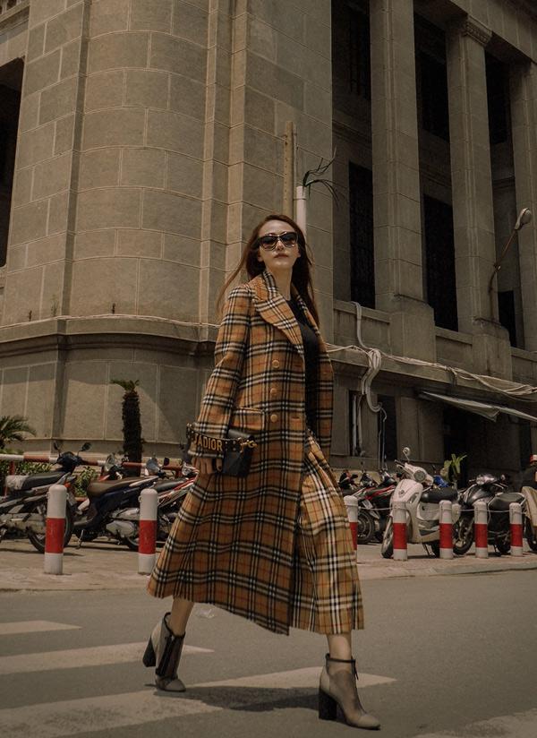 Ngân Khánh gợi ý trang phục cho mùa Thu Đông 2018. Cô mặc áo khoác dài, bốt cổ ngắn, túi xách hàng hiệu sải bước ở Sài Gòn.