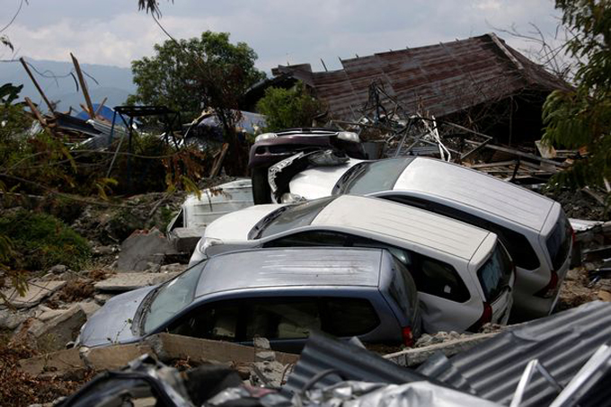 A damaged cars sit in a tsunami devastated area at Petobo village