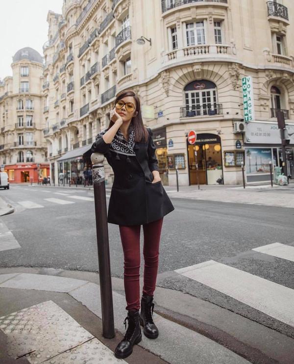 Phong cách mùa thu cho nàng công sở hiện đại với cách phối áo vest đen, jeans ống ôm tông đỏ rượu chat đi cùng bốt đen.