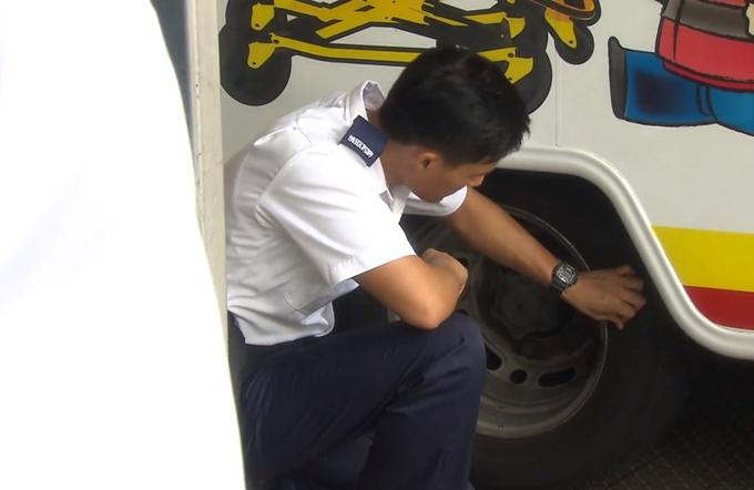Một nhân vật trong xe dùng tay không kiểm tra lốp xe