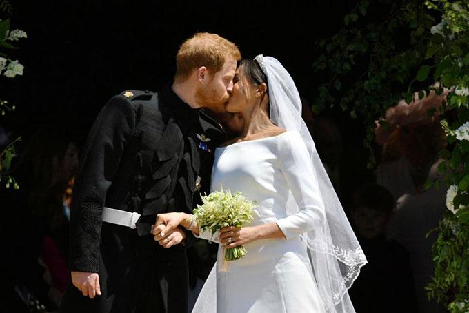 Hoàng tử Harry hôn cô dâu Meghan trước cửa nhà nguyện St. George, lâu đài Windsor ngày 19/5. Ảnh: UK Press.