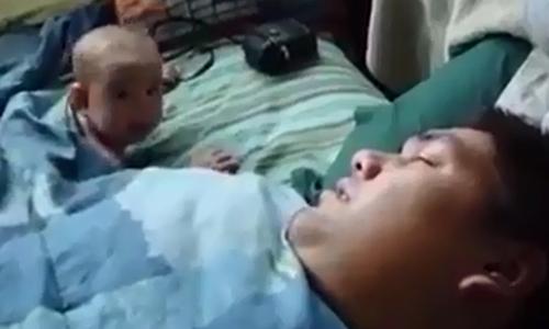 Em bé đang ngủ giật bắn mình vì tiếng ngáy của bố