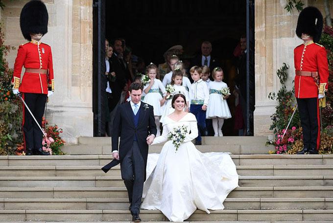 Cặp vợ chồng nắm tay nhau bước xuống các bậc thang trước cửa nhà nguyện để chuẩn bị lên xe ngựa đi chào người dân. Đây cũng là nơi mà Hoàng tử Harry và Meghan Markle kết hôn từ 5 tháng trước.