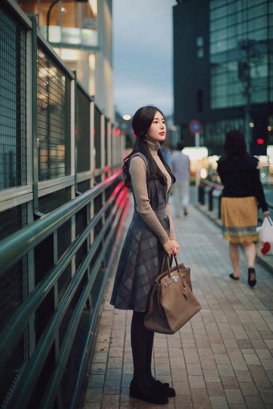 Đến văn phòng vào mùa này, các bạn gái ở Hà Nội có thể áp dụng cách phối áo cổ lọ dệt kim cùng váy kẻ sọc ca rô, quần tất để tạo dựng hình ảnh quý cô mùa thu.