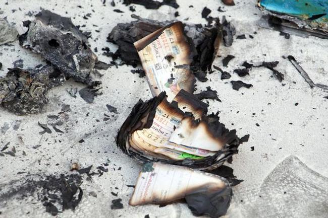 Những tấm vé số trượt giải cháy dở được tìm thấy trong túi của ông Peerapong Jirakunarat ở đền Wat Sutthawat, Pattaya, Thái Lan, sáng 11/10. Ảnh: Viral Press.