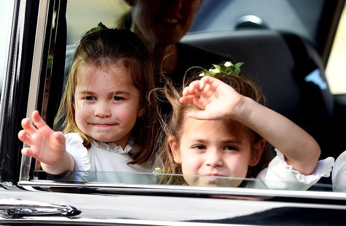Trước đó, khi ngồi trên xe để tới nhà nguyện, Công chúa Charlotte liên tục thò tay ra bên ngoài cửa sổ để vẫy tay chào người dân.