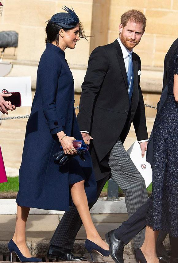 Vợ chồng Hoàng tử Harry nắm tay nhau xuất hiện tại đám cưới em họ Eugenie ở lâu đài Windsor hôm 12/10. Ảnh: EPA.