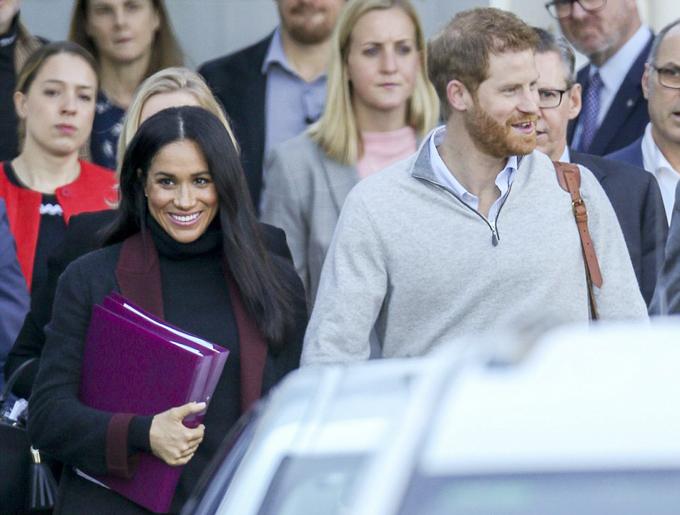 Nữ công tước xứ Sussex dùng hai tập tài liệu màu tím che bụng khi đến Sydney sáng 15/10. Ảnh: Media-Mode.