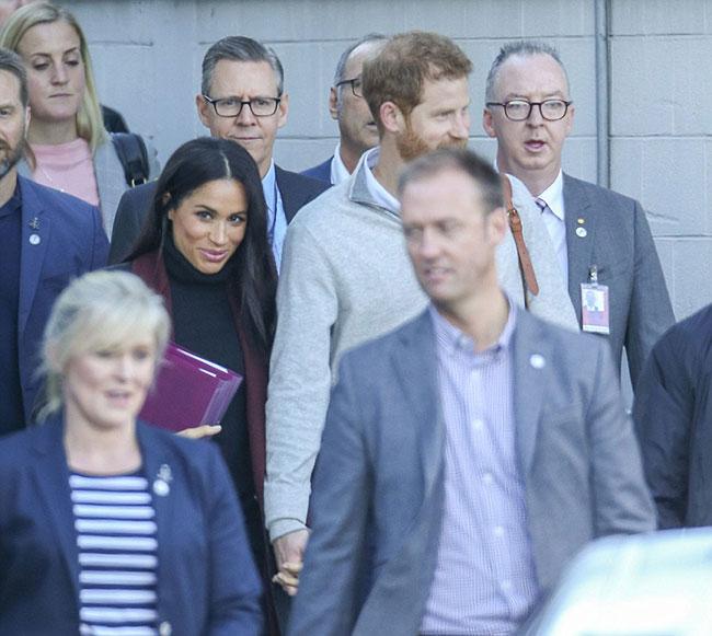 Meghan ôm tài liệu che bụng, nắm chặt tay chồng khi hạ cánh xuống sân bay Sydney, Australia sáng sớm 15/10. Ảnh: Media-mode.
