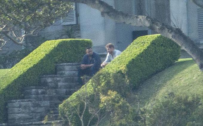 Hoàng tử Harry trò chuyện với một người đàn ông được cho là nhân viên bảo vệ bên thềm dinh thự Admiralty House bên bờ sông Sydney. Ảnh: Nine.