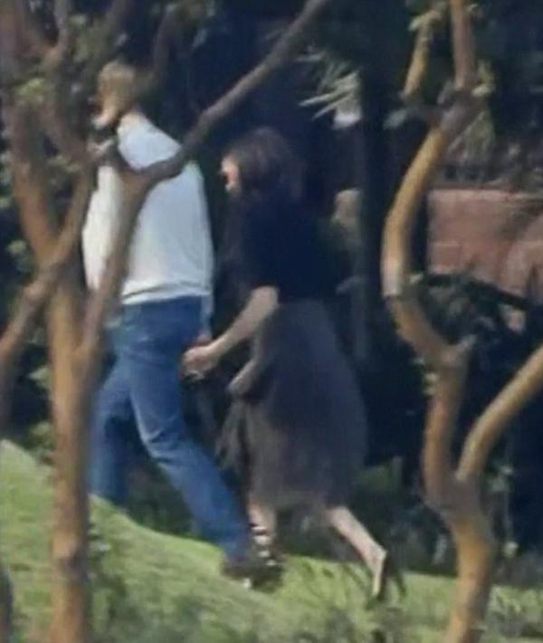 Harry nắm tay vợ cẩn thận qua đoạn cỏ dốc khi đi tham quan dinh thự Admiralty House bên sông. Ảnh: Nine.
